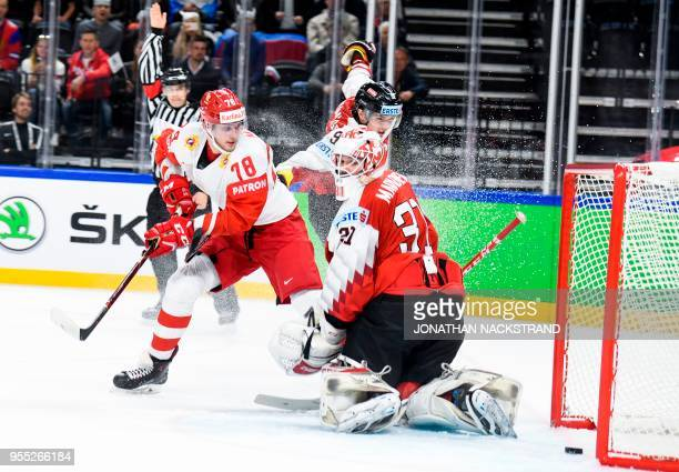 Russia's Maxim Mamin strikes to score past Austria's goalie David Madlener during the group A match Austria vs Russia of the 2018 IIHF Ice Hockey...