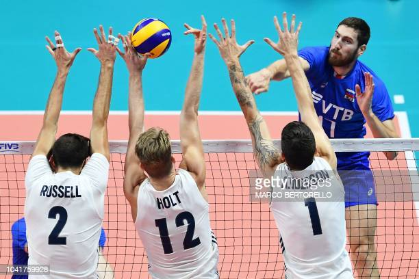 Russia's Maxim Mikhaylov hits the ball as USA's players Aaron Russell Maxwell Holt and Matthew Anderson try to block the ball as they compete in the...