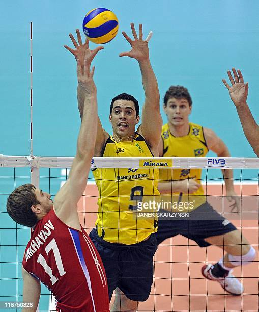Russia's Maxim Mikhaylov spikes the ball against Brazil's Lope Theo and Rezede Bruno Mossa during their Volleyball World League gold medal game in...