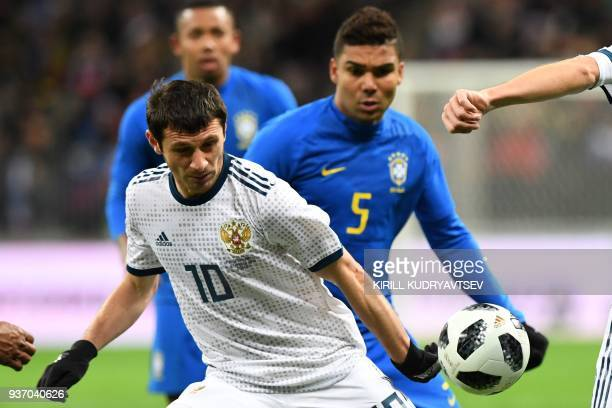 Russia's midfielder Alan Dzagoev and Brazil's midfielder Casemiro vie for the ball during an international friendly football match between Russia and...