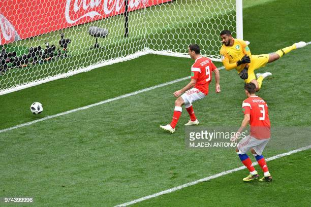 Russia's midfielder Alan Dzagoev and Russia's defender Ilja Kutepov watch a goal by midfielder Yuri Gazinskiy pass Saudi Arabia's goalkeeper Abdullah...