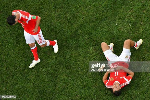 Russia's midfielder Alan Dzagoev and Russia's midfielder Roman Zobnin react at the end of the penalty shootouts of the Russia 2018 World Cup...