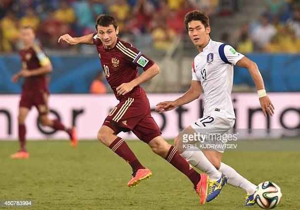 Russia's midfielder Alan Dzagoev and South Korea's defender Lee Yong vie during the Group H football match between Russia and South Korea in the...