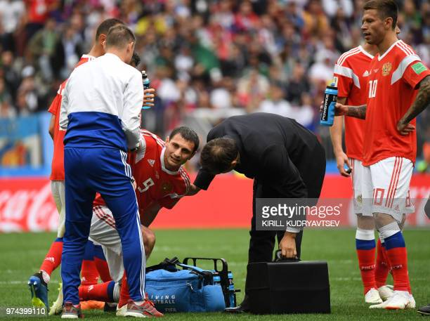 Russia's midfielder Alan Dzagoev is treated by medical staff after being injured during the Russia 2018 World Cup Group A football match between...