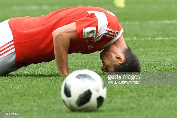 Russia's midfielder Alan Dzagoev reacts due to an injury during the Russia 2018 World Cup Group A football match between Russia and Saudi Arabia at...