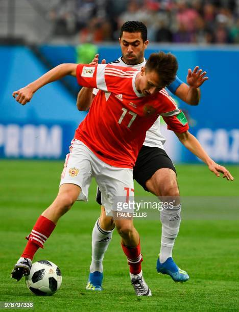 Russia's midfielder Aleksandr Golovin and Egypt's defender Ahmed Fathi vie during the Russia 2018 World Cup Group A football match between Russia and...