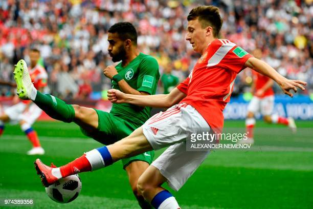 Russia's midfielder Aleksandr Golovin and Saudi Arabia's defender Mohammed AlBreik vie for the ball during the Russia 2018 World Cup Group A football...