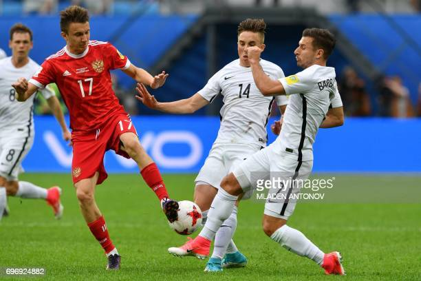 Russia's midfielder Alexander Golovin is tackled by New Zealand's midfielder Ryan Thomas and New Zealand's forward Kosta Barbarouses during the 2017...