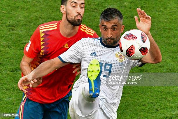 TOPSHOT Russia's midfielder Alexander Samedov vies for the ball with Spain's midfielder Sergio Busquets during the Russia 2018 World Cup round of 16...