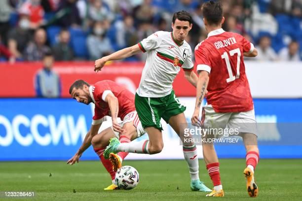 Russia's midfielder Alexei Ionov, Bulgaria's midfielder Birsent Karagaren and Russia's midfielder Aleksandr Golovin vie for the ball during the...