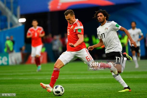 Russia's midfielder Denis Cheryshev and Egypt's midfielder Mohamed Elneny vie during the Russia 2018 World Cup Group A football match between Russia...