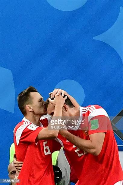 TOPSHOT Russia's midfielder Denis Cheryshev celebrates with teammate Russia's forward Artem Dzyuba after scoring during the Russia 2018 World Cup...