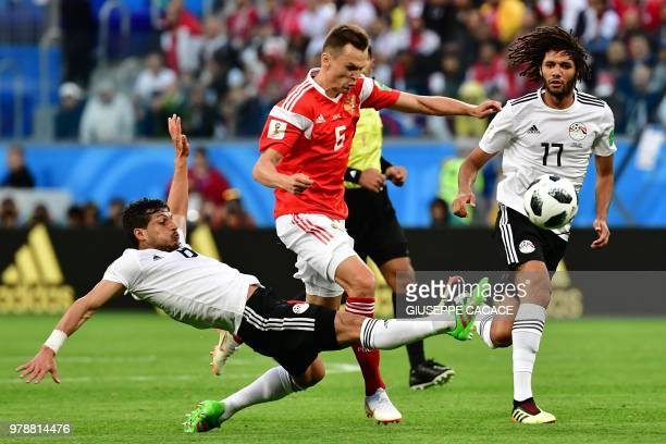 Russia's midfielder Denis Cheryshev fights for the ball with Egypt's midfielder Tarek Hamed and Egypt's midfielder Mahmoud 'Kahraba' AbdelMoneim...