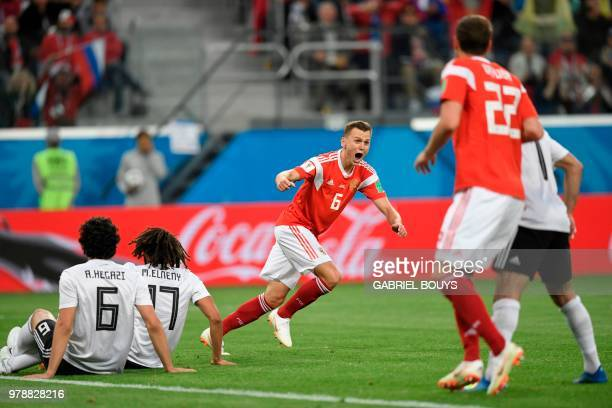 TOPSHOT Russia's midfielder Denis Cheryshev reacts after scoring the 20 goal during the Russia 2018 World Cup Group A football match between Russia...
