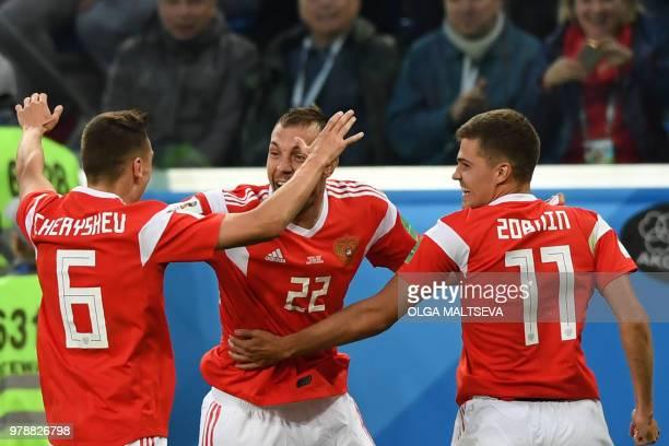 Russia's midfielder Denis Cheryshev Russia's forward Artem Dzyuba and Russia's midfielder Roman Zobnin celebrate after Egypt's defender Ahmed Fathi...