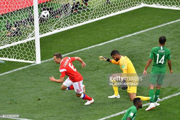 Russia's midfielder Denis Cheryshev scores a goal past Saudi Arabia's goalkeeper Abdullah AlMayouf during the Russia 2018 World Cup Group A football...