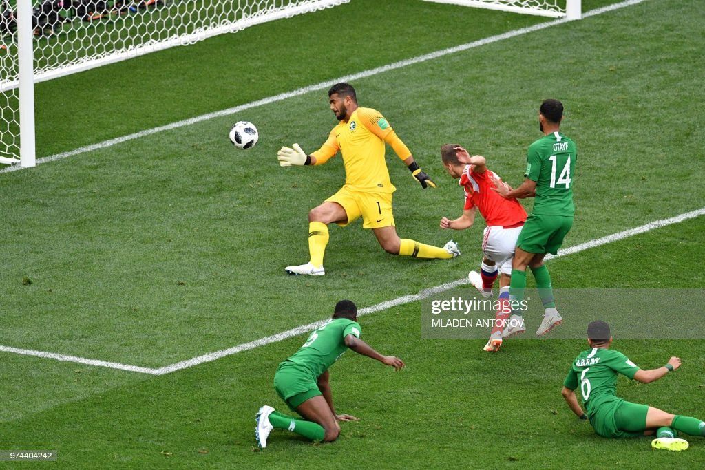 TOPSHOT - Russia's midfielder Denis Cheryshev (C) scores a goal past Saudi Arabia's goalkeeper Abdullah Al-Mayouf during the Russia 2018 World Cup Group A football match between Russia and Saudi Arabia at the Luzhniki Stadium in Moscow on June 14, 2018. (Photo by Mladen ANTONOV / AFP) / RESTRICTED