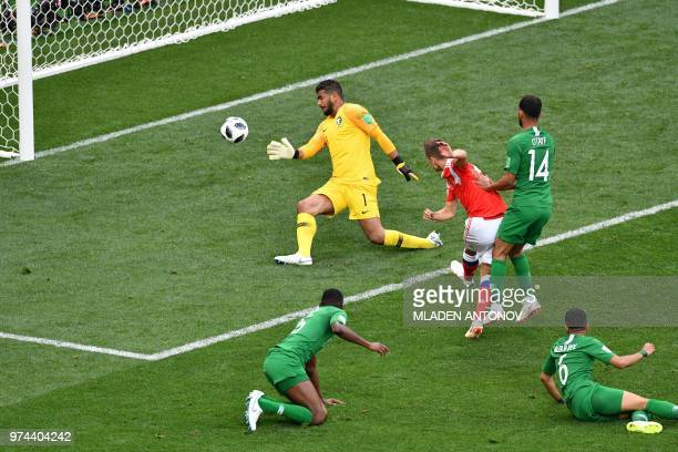 TOPSHOT Russia's midfielder Denis Cheryshev scores a goal past Saudi Arabia's goalkeeper Abdullah AlMayouf during the Russia 2018 World Cup Group A...