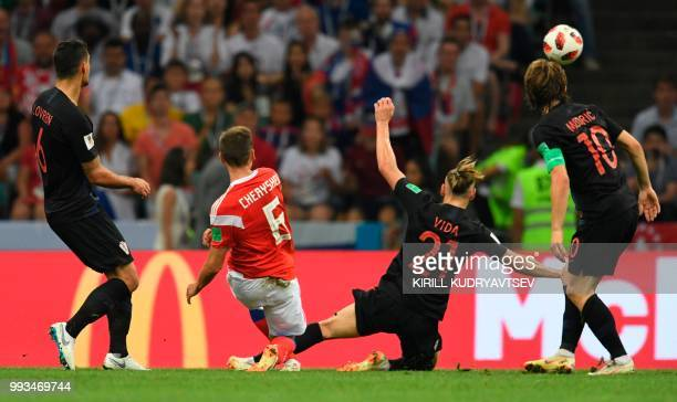 TOPSHOT Russia's midfielder Denis Cheryshev shoots to score the opening goal during the Russia 2018 World Cup quarterfinal football match between...