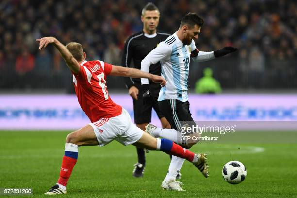 Russia's midfielder Denis Glushakov and Argentina's Lionel Messi vie for the ball during an international friendly football match between Russia and...