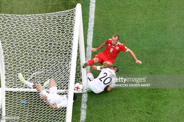 Russia's midfielder Denis Glushakov scores the match's first goal as he is tackled by New Zealand's defender Michael Boxall and New Zealand's...