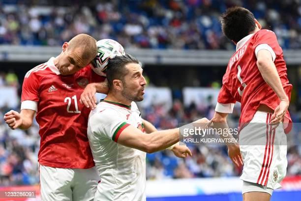 Russia's midfielder Dmitri Barinov, Bulgaria's striker Andrey Galabinov and Russia's defender Vyacheslav Karavayev vie for the ball during the...