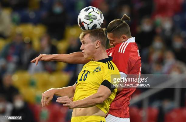 Russia's midfielder Magomed Ozdoev vies with Swedish defender Emil Krafth during the international friendly football match Russia v Sweden in Moscow,...