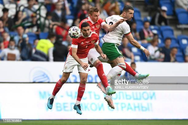 Russia's midfielder Magomed Ozdoyev, Russia's defender Andrey Semyonov and Bulgaria's striker Andrey Galabinov vie for the ball during the friendly...