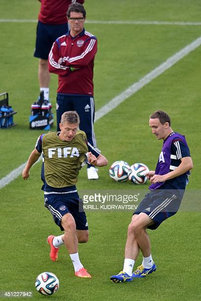 Russia's midfielder Oleg Shatov and Russia's defender Aleksei Kozlov take part in a training session at the Antonio Couto Pereira stadium in Curitiba...