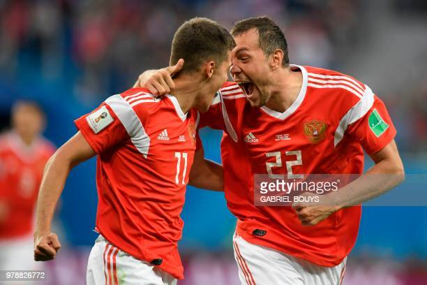 Russia's midfielder Roman Zobnin and Russia's forward Artem Dzyuba celebrate the opening goal during the Russia 2018 World Cup Group A football match...