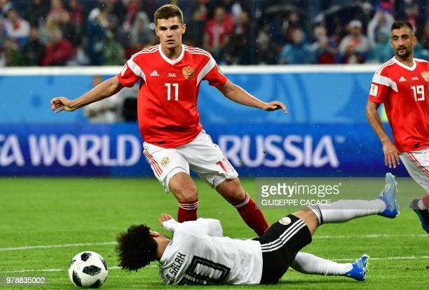 Russia's midfielder Roman Zobnin makes a fault on Egypt's forward Mohamed Salah during the Russia 2018 World Cup Group A football match between...