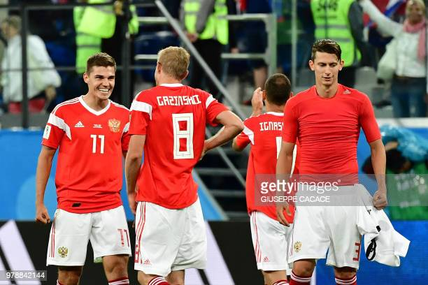 Russia's midfielder Roman Zobnin Russia's midfielder Yuri Gazinskiy and Russia's defender Ilja Kutepov celebrate after winning 31 the Russia 2018...