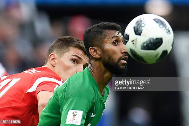 Russia's midfielder Roman Zobnin vies with Saudi Arabia's midfielder Salman AlFaraj during the Russia 2018 World Cup Group A football match between...