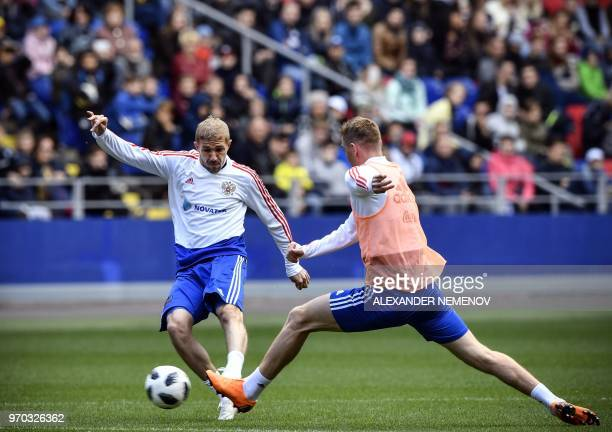 Russia's midfielder Yuri Gazinskiy and Russia's defender Andrey Semyonov vie for the ball during a training session at Moscow's VEB Arena stadium on...