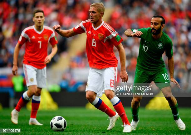 Russia's midfielder Yuri Gazinskiy and Saudi Arabia's forward Mohammed AlSahlawi R0 vie during the Russia 2018 World Cup Group A football match...