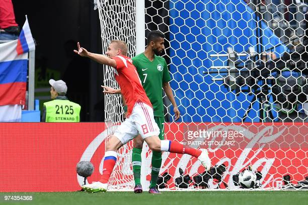 Russia's midfielder Yuri Gazinskiy celebrates a goal past Saudi Arabia's midfielder Salman AlFaraj during the Russia 2018 World Cup Group A football...