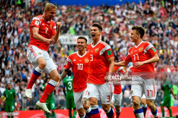 TOPSHOT Russia's midfielder Yuri Gazinskiy celebrates scoring the opening goal with his teammates during the Russia 2018 World Cup Group A football...