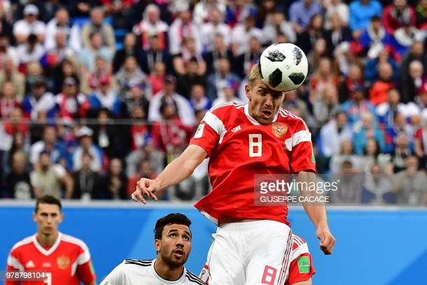 TOPSHOT Russia's midfielder Yuri Gazinskiy heads the ball during the Russia 2018 World Cup Group A football match between Russia and Egypt at the...