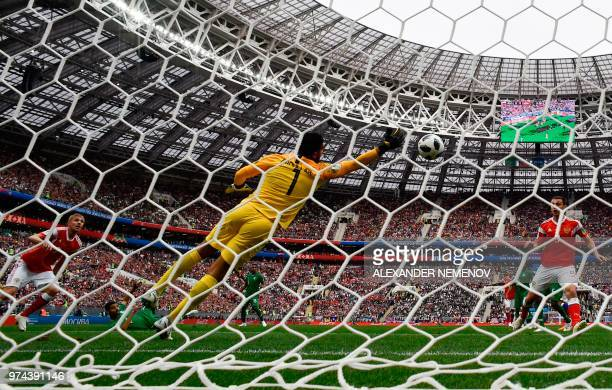TOPSHOT Russia's midfielder Yuri Gazinskiy scoring the opening goal past Saudi Arabia's goalkeeper Abdullah AlMayouf during the Russia 2018 World Cup...