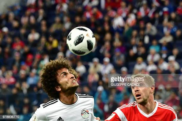 Russia's midfielder Yuri Gazinskiy vies with Egypt's midfielder Amr Warda during the Russia 2018 World Cup Group A football match between Russia and...