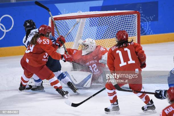 Russia's Nadezda Morozova is hit with the stick of Finland's Emma Nuutinen in the women's bronze medal ice hockey match between Finland and the...