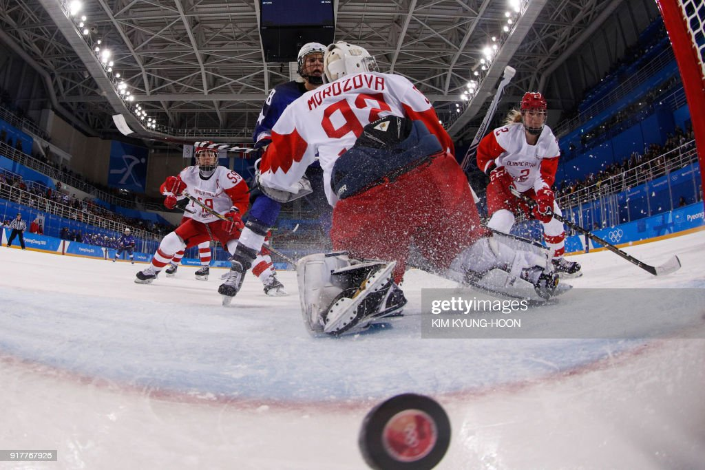 TOPSHOT - Russia's Nadezda Morozova (C) lets in a goal by USA's Kacey Bellamy in the women's preliminary round ice hockey match between the US and Olympic Athletes from Russia during the Pyeongchang 2018 Winter Olympic Games at the Kwandong Hockey Centre in Gangneung on February 13, 2018. /