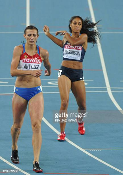 Russia's Natalya Antyukh and US athlete Queen Harrison finish their women's 400 metres hurdles semifinal at the International Association of...