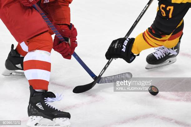 Russia's Nikolai Prokhorkin and Germany's Marcel Goc fight for the puck in the men's gold medal ice hockey match between the Olympic Athletes from...