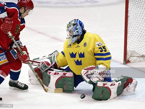 Russia's Nikolai Pronin shot is blocked by Sweden's goalie Henrik Lundqvist during the Russia-Sweden match, part of the eurohockey Karjala Cup in...