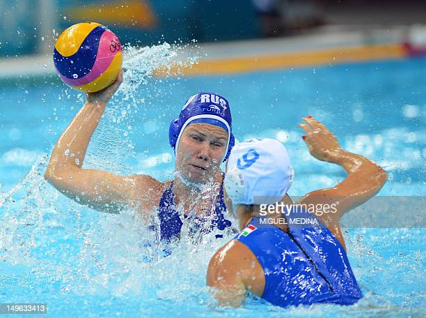 Russia's Olga Beliaeva is challenged by Italy's Giulia Rambaldi during the women's water polo preliminary round groupe B match between Italy and...