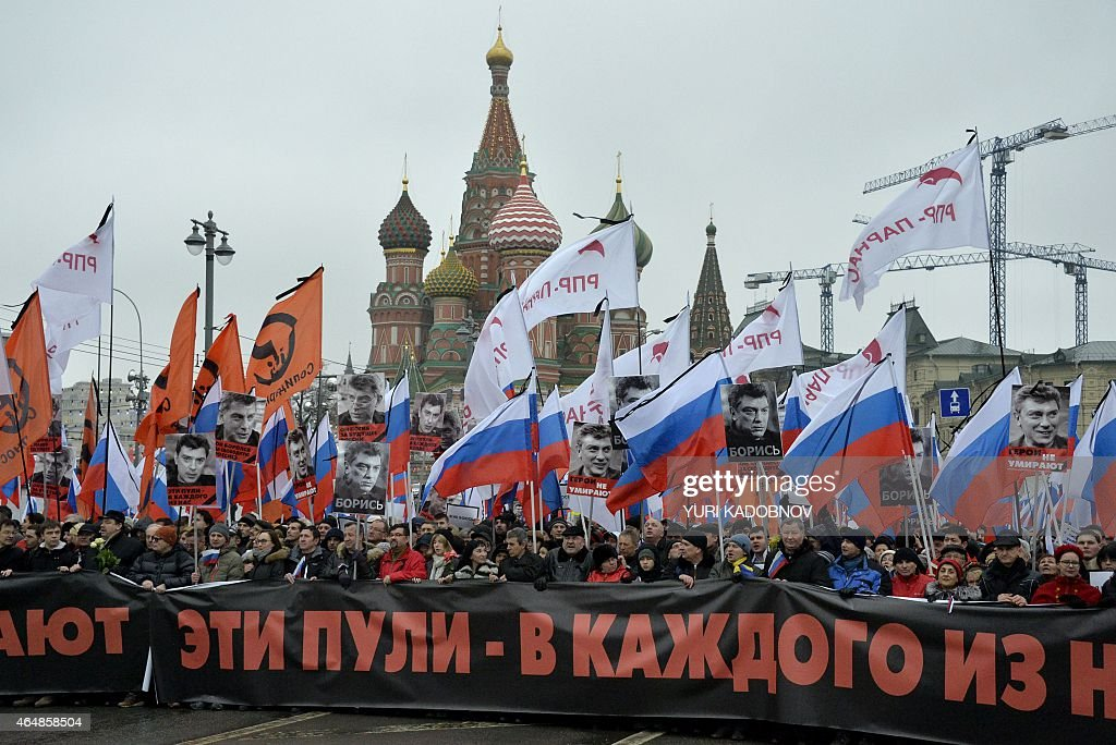 Russia's opposition supporters carry a banner reading These bullets in each of us during a march in memory of murdered Kremlin critic Boris Nemtsov in central Moscow on March 1, 2015. The 55-year-old former first deputy prime minister under Boris Yeltsin was shot in the back several times just before midnight on February 27 as he walked across a bridge a stone's throw from the Kremlin walls.