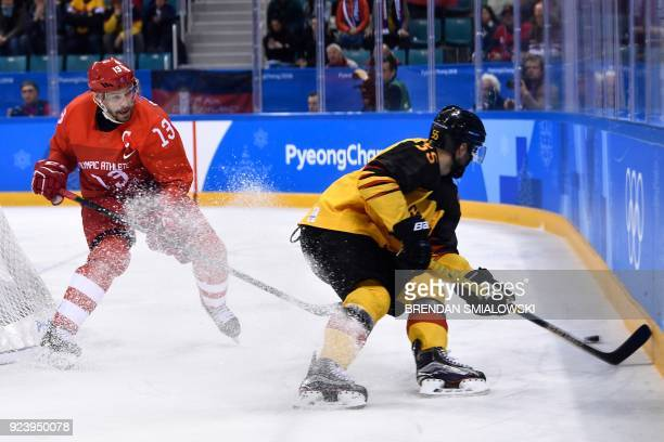 Russia's Pavel Datsyuk and Germany's Felix Schutz fight for the puck in the men's gold medal ice hockey match between the Olympic Athletes from...