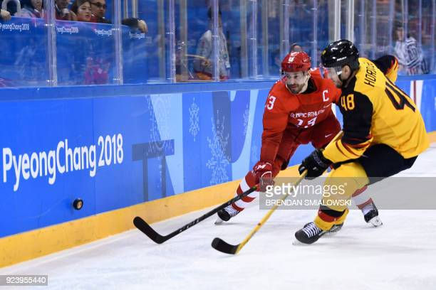 Russia's Pavel Datsyuk and Germany's Frank Hordler fight for the puck in the men's gold medal ice hockey match between the Olympic Athletes from...