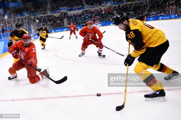 TOPSHOT Russia's Pavel Datsyuk and Germany's Frank Hordler fight for the puck in the men's gold medal ice hockey match between the Olympic Athletes...